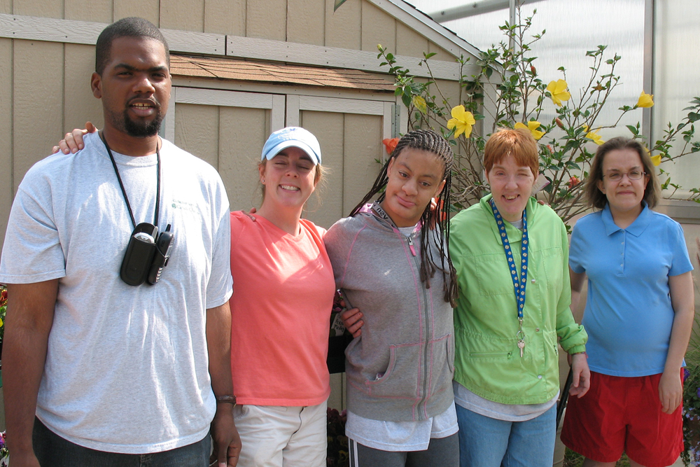 Three women and one man with intellectual disability stand with a volunteer at Gallagher