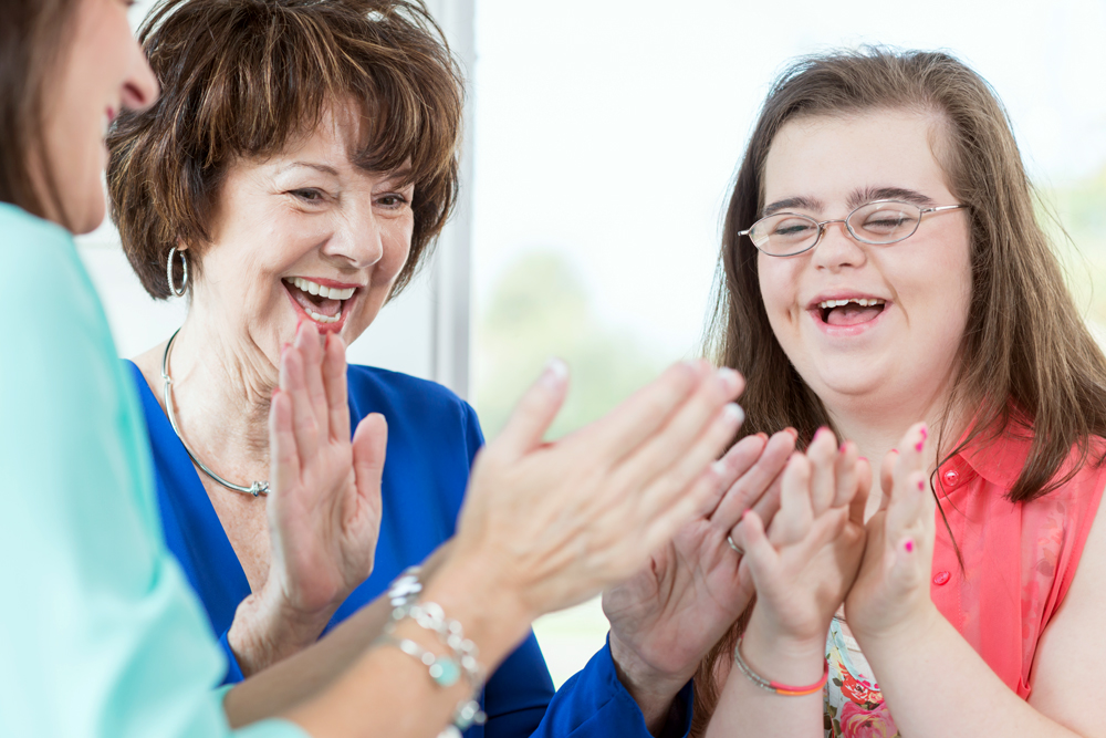 A young adult with intellectual disability plays a hand game with two women.